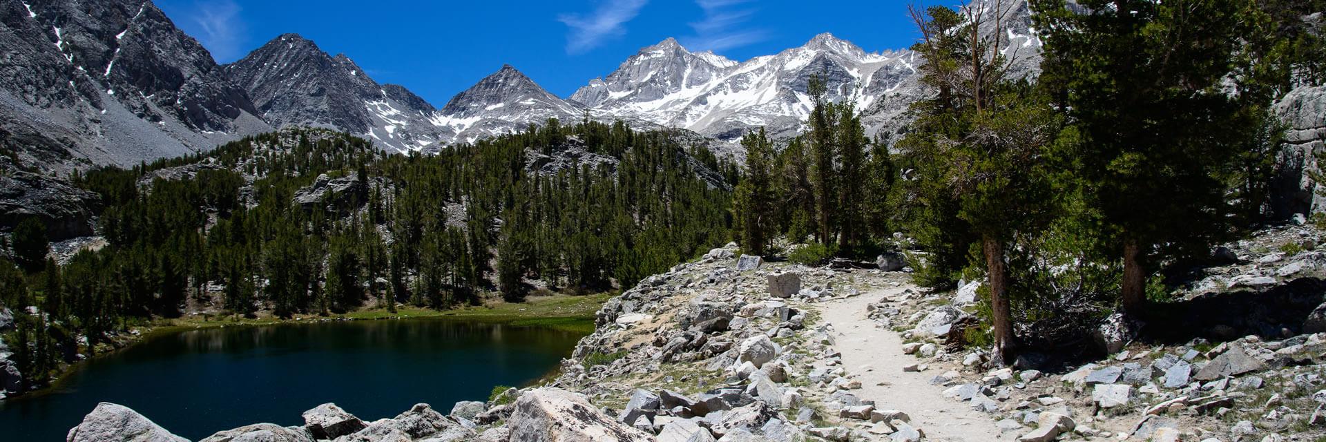 Rocky trail alongside a lake heading towards the Sierra Nevada mountains