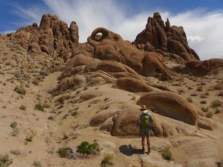 Hiker at the bottom of a hill with Mobius Arch above