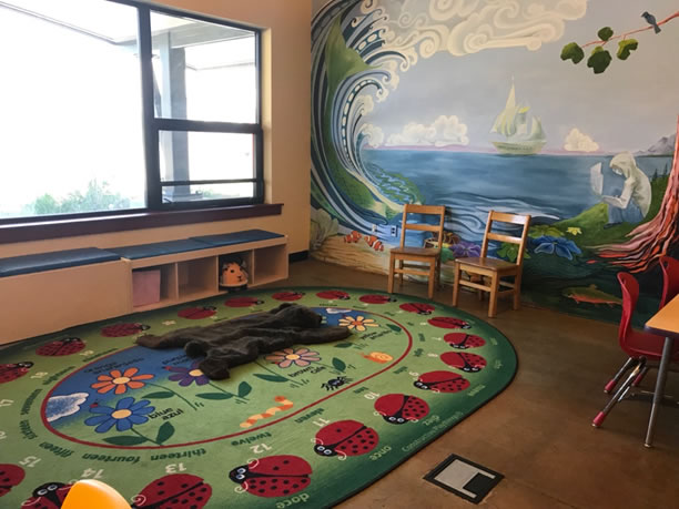 Room with colorful rug and mural for childrens storytime