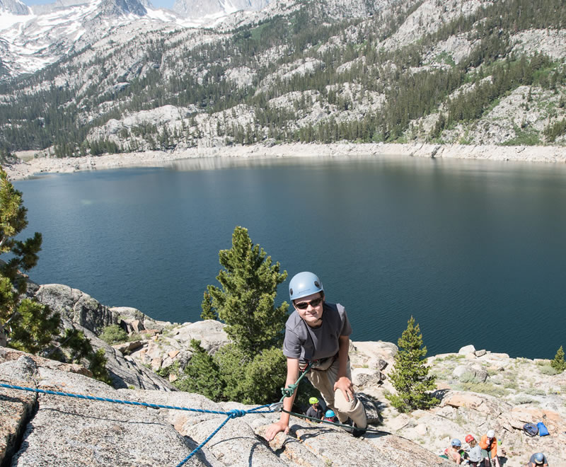 Woman rock climbing above a mountain lake