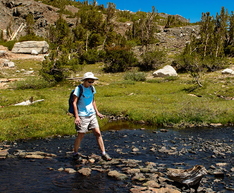 Hiker in backcountry sierra crossing a stream