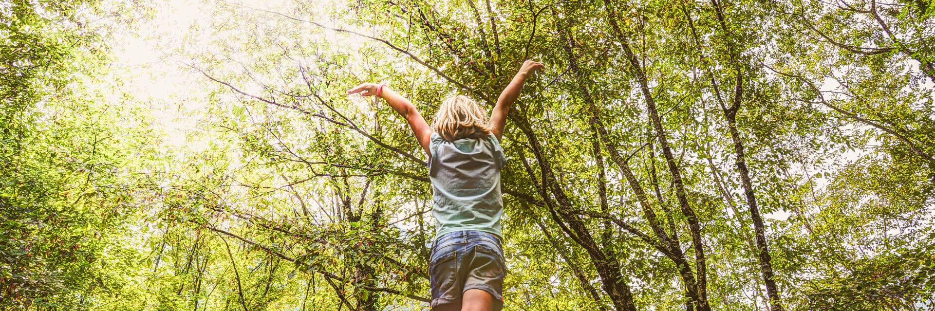 Young child in tree area with arms raised